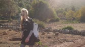 греческий : Hiker woman with backpack walking along the road strewn with small stones