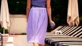 фрак : Young woman in long skirt and sneakers walking by the swimming pool, back side view