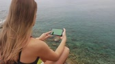 zigeuners : Female tourist taking pictures on mobile phone sitting on a rock on clear sky and calm Mediterranean sea background. Catching good moments of life