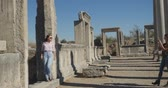 open air museum : Young tourist taking picture in Ancient city Perge with antique colonnada ruins of ancient temple roman architecture on background. This is open air antique historical museum in Turkey Stock Footage