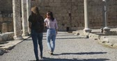 régészet : Young women tourist walking in Ancient city Perge with antique colonnada ruins of ancient temple roman architecture on background. This is open air antique historical museum in Turkey