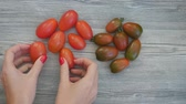 de baixa caloria : Closeup of womans hands put different color cherry tomatoes in the shape of a heart on a white background in fast motion. Healthy food concept