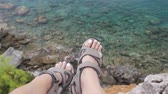 тапочка : Woman with trekking sandals sitting on rock high above the sea Стоковые видеозаписи