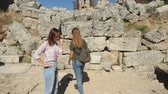 anfiteatro : Young women tourist walking with map in Ancient city Perge with antique colonnada ruins of ancient temple roman architecture on background. This is open air antique historical museum in Turkey Stock Footage