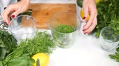 rúcula : Womans hands preparing healthy green cocktail adding water and mixing ingredients using hand blender. Healthy eating concept. Greenery on white table.