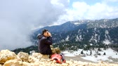 alt : Hiker looking at binoculars at amazing view near the 2365m high Tahtali mountain peak in Turkey, Antalya province.