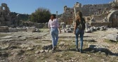 open air museum : Young women tourist walking in Ancient city Perge with antique colonnada ruins of ancient temple roman architecture on background. This is open air antique historical museum in Turkey