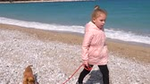 привязь : Little girl walking her cocker spaniel puppy on the leash by the seaside