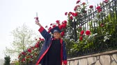 profesor : Happy caucasian child in graduation gown with diploma joyfully dancing and throwing mortarboard near fence full of wild roses. Students celebration graduation, education concept