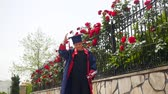 diplôme : Happy caucasian child in graduation gown with diploma joyfully dancing and throwing mortarboard near fence full of wild roses. Students celebration graduation, education concept