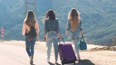 excesso de velocidade : Three young girls tourists in jeans clothes walking down the road with beautiful mountain view Vídeos
