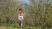 гармония : Young beautiful caucasian woman in long dress in bay leaf wreath running happily in spring blossom plum garden.