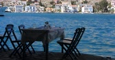 Киклады : wooden table and chairs prepared for clients by the sea coast of Kastellorizo, Greece. Beautiful background.