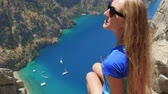бабочки : Young woman traveler with blond hair and sunglasses enjoying beautiful view of The Butterfly Valley from the top of the mountain, The Butterfly Valley in the city of OludenizFethiye in western Turkey