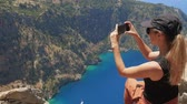 motýlek : Young woman traveler with blond hair and sunglasses enjoying beautiful view of The Butterfly Valley from the top of the mountain. The Butterfly Valley in the city of OludenizFethiye in western Turkey