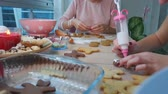 cardamom : Young girls decorates ginger cookies Christmas winter evening. Women icing ornament with white glaze