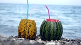 melones : Two womans hands take sweet summer days fresh watermelon bowl cocktail on the marble beach with sea waves on background Archivo de Video