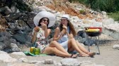 passievrucht : Young beautiful girls in sunglasses drinking fresh coconut cocktails while sitting on the sand beach. There is ear of corn on the grill and a lot of stones on background Stockvideo
