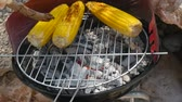 tradicionalmente : Grilling ears of corn on charcoal process. Summer chill and farm food concept