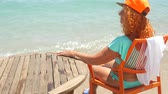 若々しい : Youthful 78 years old woman enjoying her life sitting in blue bikini and orange cap by the sea