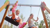 dromer : Sisters swinging together on playground. Summer time, southern country, having fun