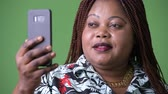 tranças : Overweight beautiful African woman against green background
