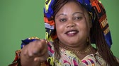 orta yetişkin kadın : Overweight beautiful African woman wearing traditional clothing against green background