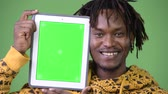 dijital tablet : Young happy handsome African man showing digital tablet