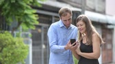partneři : Young happy couple using phone together outdoors