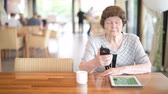 ponderando : Senior Woman Using Phone While Thinking At The Coffee Shop Stock Footage
