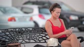beira da estrada : Mature Beautiful Tourist Woman Using Phone While Sitting On The Bench Stock Footage