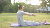 full body shot : Profile view of young man doing yoga while sitting at the park Stock Footage