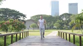 jogging yapan : Healthy young man jogging towards wooden bridge at the park