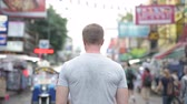 khaosan : Rear view of young tourist man looking around Khao San road in Bangkok