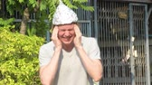 teoria : Stressed young man with tinfoil hat as conspiracy theory concept panicking outdoors