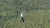 slackliner : A man walks on a rope stretched at an altitude between two peaks in the Siberian nature reserve Stolby. Stock Footage