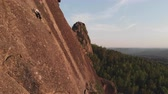 aperto : Aerial view of the people climb to the top of the rock in the Siberian nature reserve Stolby.