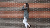 un : Young woman dancing against a brick wall walking around the city.