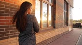 bizakodó : A young woman walks the streets of the city at sunset.