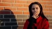 cigar : Portrait of a young woman Smoking a cigarette looking at the camera.