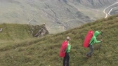 альпинист : Aerial shot of a group of tourists with backpacks climb the mountain.