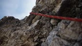 góral : Climbing rope hanging on a rock close-up. Equipment climbers in the mountains, steadicam shot.