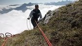 держать : Climber working with equipment in the mountains.
