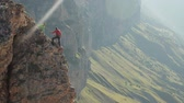 話し合う : A group of climbers discussing a plan of action standing on the edge of the cliff. 動画素材
