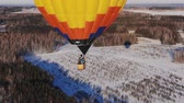 авиация : Aerial shot of the people fly on a big bright balloon over the winter forest.