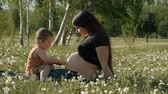 A young pregnant woman and her son are sitting happily on a flower meadow.