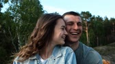 lachend : Slow motion portraits of a happy young couple. An attractive woman smiles and kisses her boyfriend. Stockvideo
