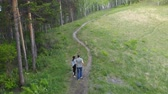Aerial shot of a young couple running down a forest path. Wideo