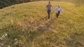 Aerial shot of a young couple happily running across a mountain meadow at sunset.