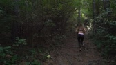 antreman : Young female exercising in green forest outdoors, trail running in sports outfit Stok Video